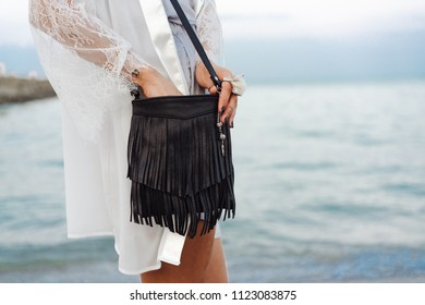 beautiful young girl with a handbag posing by the sea at the camera