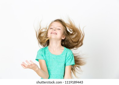 beautiful young girl is happy and dancing and posing in the studio in front of white background