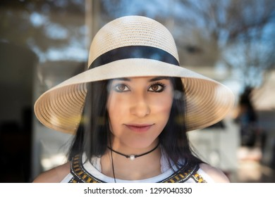 Beautiful young girl in hat looking through window