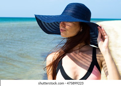beautiful young girl in a hat on the beach in Ocean
