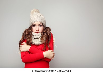 Beautiful young girl in hat and scarf on grey background