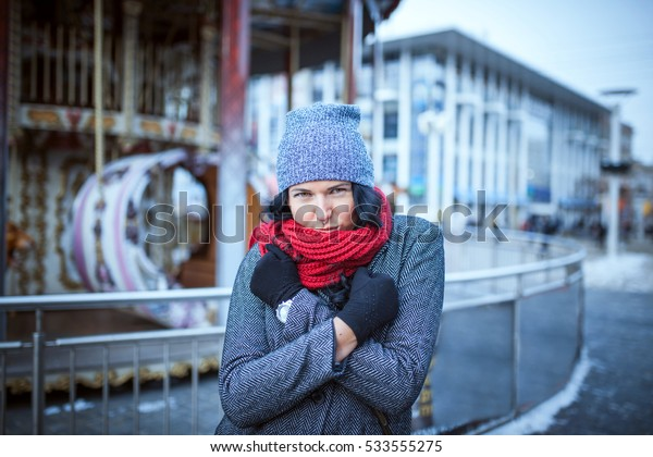 Beautiful and young girl in a hat walking in the evening city