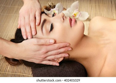 Beautiful young girl having face massage in spa salon