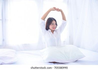 Beautiful young girl having fun and holding pillow on a white bed.