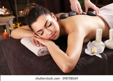 Beautiful young girl having massage with stones in spa salon