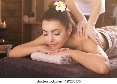 Beautiful young girl having massage in spa salon