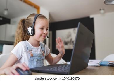 schönes junges Mädchen mit Headset sitzt während der Corona-Zeit vor ihrem Laptop