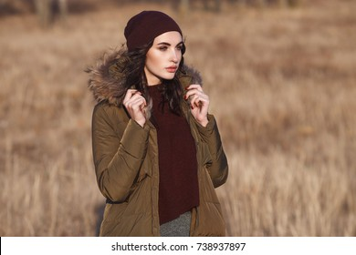 Beautiful Young  Girl in her Winter Warm Fashion Clothing. Down jacket and warm hat. Casual style.