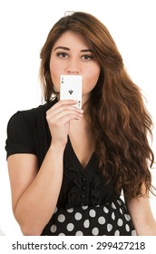 Beautiful young girl holding ace of clubs card in front of her mouth isolated on white