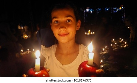 Beautiful young girl holding apple candles iluminating her face in the dark in a waldorf school christmas advent celebration