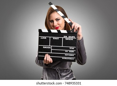 Beautiful young girl holding a clapperboard on textured background