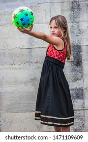 beautiful young girl holding a colorful toy ball