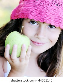 A beautiful young girl holding a delicious green apple