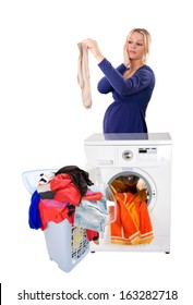 Beautiful young girl holding a dirty men's sock. Next to a washing machine and a pile of dirty laundry. Isolated on white background.