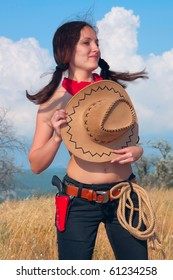 beautiful young girl holding hat in his hands, flirty, cowboy