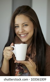 Beautiful young girl holding hot chocolate and smiling in front of the camera