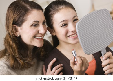 A beautiful young girl holding a mirror and a tube of lipstick with her mother.  They are smiling.  Horizontally framed shot.