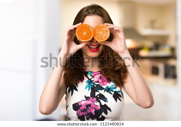 Beautiful young girl holding oranges on unfocused background