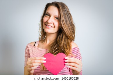 beautiful young girl holding paper heart in her hands isolated on white background