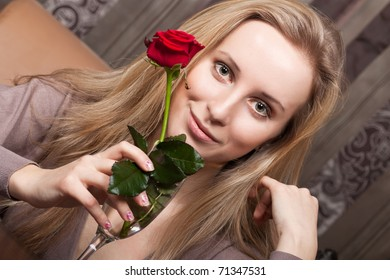 Beautiful young girl holding a red rose