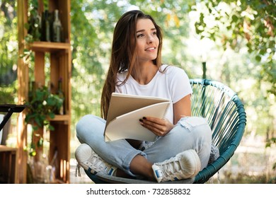 Beautiful young girl holding a textbook while sitting in a chair and looking away outdoors