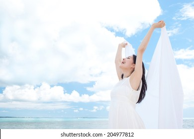 Beautiful young girl holding white cloth on tropical island beach