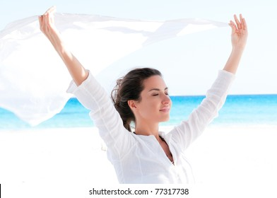 Beautiful young girl holding white fabric at wind in a summer vacation