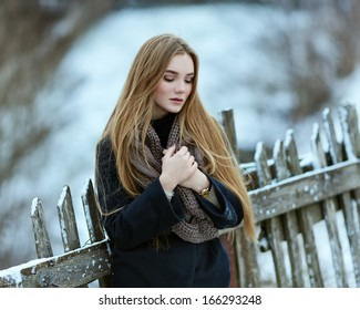 Beautiful young girl hot. Winter near the fence