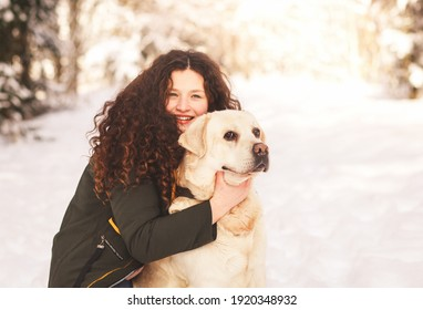 Beautiful young girl hugs dog labrador in winter in nature