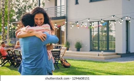 Beautiful Young Girl Hugs Her Boyfriend. Two Young People Embrace in the Backyard of a Garden on a Hot Summer Day.