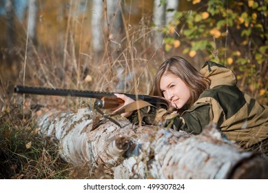 a beautiful young girl and the hunter with a gun in uniform lying on the ground in the shelter, expect the beast