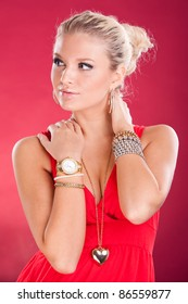 Beautiful young girl with a lot of jewelry on a red background