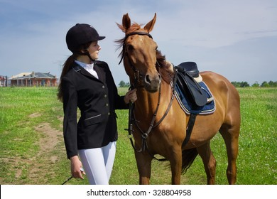 Beautiful young girl jockey talks with her horse dressing uniform competition