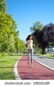 Beautiful  young girl jogging outdoor along trees path. Summer set