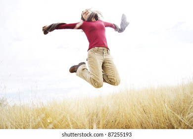 Beautiful young girl jumping with joy in a long grass field