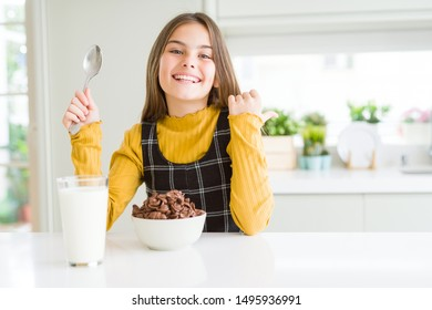Beautiful young girl kid eating chocolate cereals and glass of milk for breakfast pointing and showing with thumb up to the side with happy face smiling