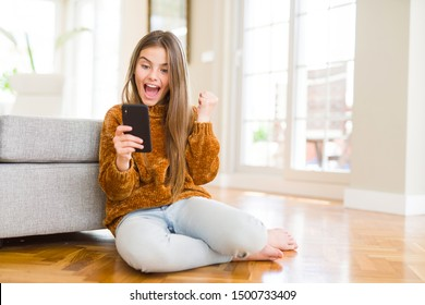 Beautiful young girl kid sending a message using smartphone screaming proud and celebrating victory and success very excited, cheering emotion