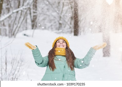A beautiful young girl in a knitted hat throws snow in the winter forest