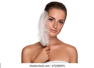 Beautiful young girl with large white feather near face. clean soft body products. Beauty Portrait. Woman Touching. Perfect Fresh Skin. Youth and Skin Care Concept. Isolated on white background