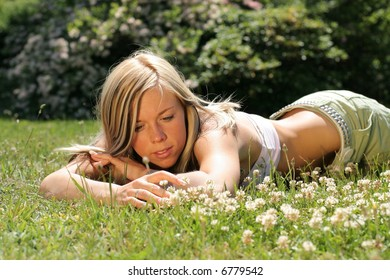 Beautiful young girl lays in the grass