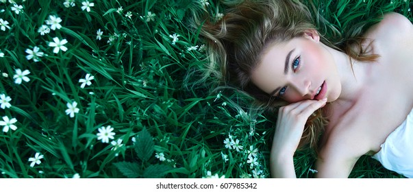 Beautiful young girl lies on a clearing among white flowers. White flowers. Chamomile. A girl with her hair in a white dress.