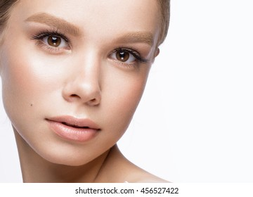 Beautiful young girl with a light natural make-up. Beauty face. Picture taken in the studio on a white background.