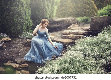 A beautiful young girl like Cinderella is walking in the garden.
