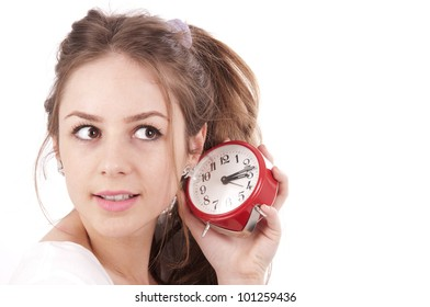 Beautiful young girl listening clock on a white background.