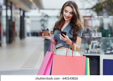 Beautiful young girl with long brown hair wearing dress standing with colorful shopping bags, cup of coffee and mobile phone, shopping concept, portrait, smiling.
