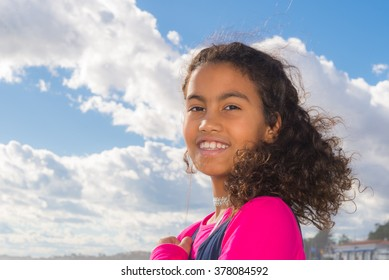 Beautiful young girl with long curly hair wearing a red t-shirt.   Portrait of happy Brazilian child against blue sky with white clouds background, pefect for family blogs and magazines