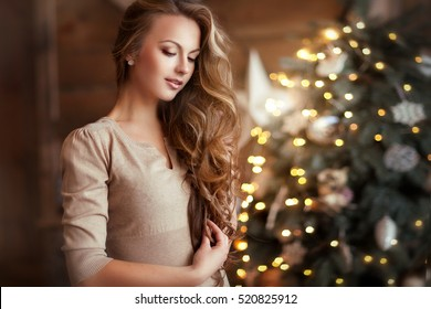 Beautiful young girl  with long curly hair standing on a christmas background with boke lights and looking down. Magic warm new year photo.