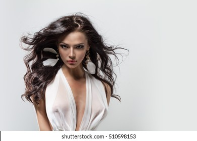 Beautiful young girl with long dark hair wearing a white dress. Portrait of a model against gray clean background, beauty style design template