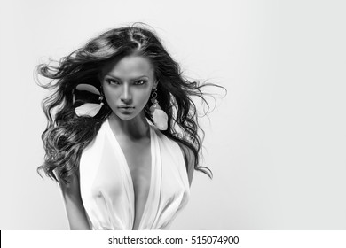 Beautiful young girl with long dark hair wearing a white dress. Portrait of a model against blue sky with white clouds background, beauty style design template