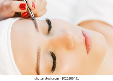 Beautiful young girl with long eyelashes tweezing her eyebrows in a beauty salon. Beauty Concept. Permanent Makeup. Microblading brow.  Beautician Doing eyebrow Tattooing. Close up view.